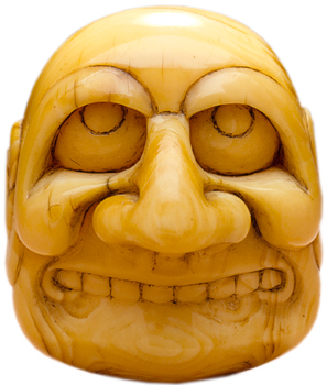 This ivory mask-shaped netsuke is from the 18th or 19th century and features sumi-ink staining.