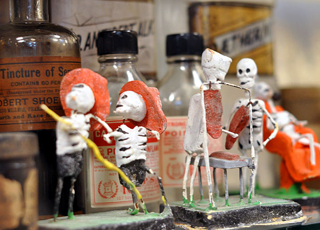 "These calaveras (Spanish for ""skull"") figurines are used in Mexican celebrations of Dia de los Muertos, also known as All Souls Day, also the origin of Halloween. At Obscura, they are posed in front of poison and medicine bottles. Via the Discovery Channel."