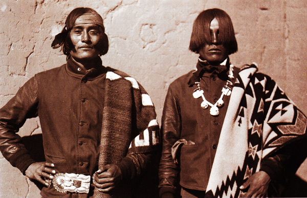 "Patricio Calabaza, left, wears a Navajo blanket, and Rafael Lobato, right, wears a Pendleton blanket, at the Santo Domingo Pueblo, circa 1930. Photo by Witter Bynner, courtesy of Museum of New Mexico, via ""Language of the Robe."""