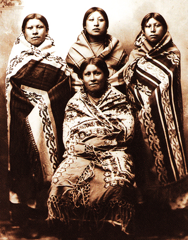 "Four young women wrapped in blankets, circa 1890. From ""Language of the Robe,"" courtesy of Western History Collections, University of Oklahoma library."