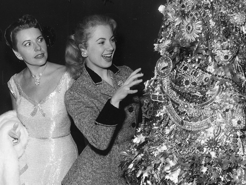 Joan Castle Joseff looks on, horrified, as Shirley Jones, who starred in many Rodgers & Hammerstein musicals, pretends to touch a Christmas tree made of Joseff jewelry during a company holiday party.