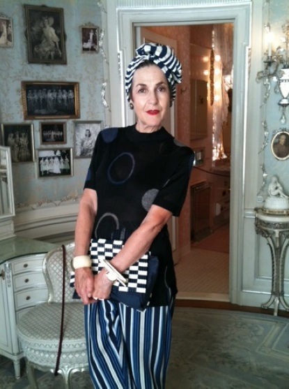 Standing in the Washington, D.C., dressing room of Marjorie Merriweather Post, Salamon wears wide Greek pajama bottoms, a Matsuda top, a 1940s checked handbag, and a polyester turban.