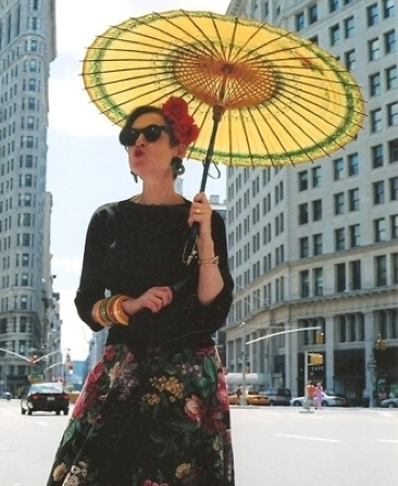 Salamon gives an air kiss to New York City in a '40s Mexican skirt with nestling Bakelite bracelets on her arm, a '30s flower clip in her hair, and a yellow Chinese parasol.