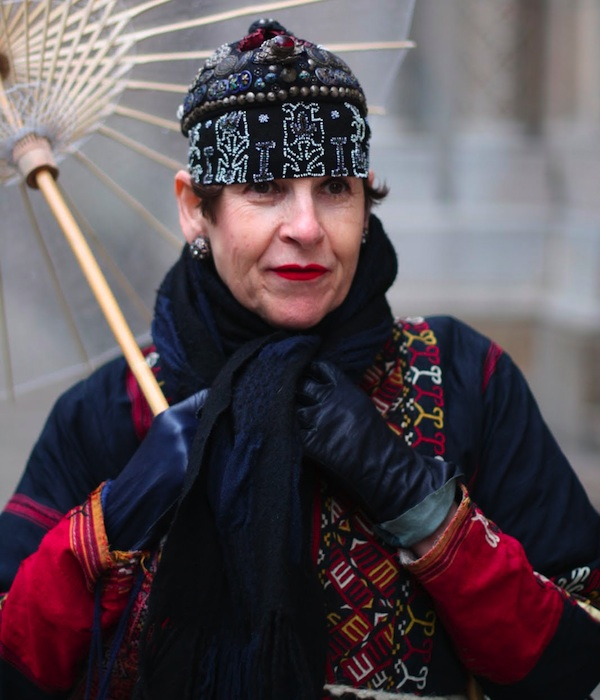 "Salamon wears an Afghani coat with two hats. The small hat on top with the silver amulets is a Bai phoenix hat from the Yunnan Province in China. Ari Seth Cohen took this photo for ""Vogue Japan,"" posted on Advanced Style."
