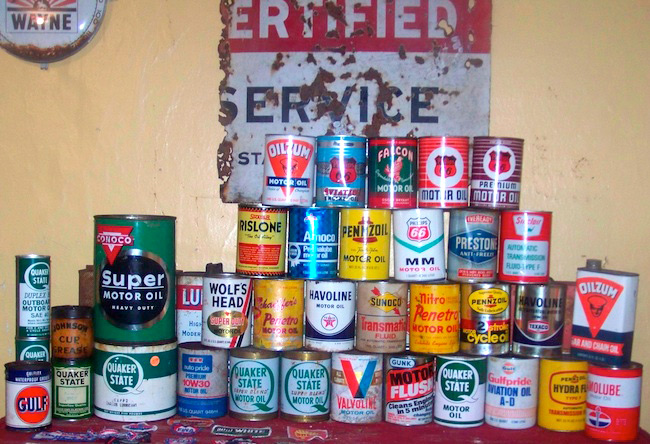 Robert displays part of his collection of oil cans and advertising signs in his home.