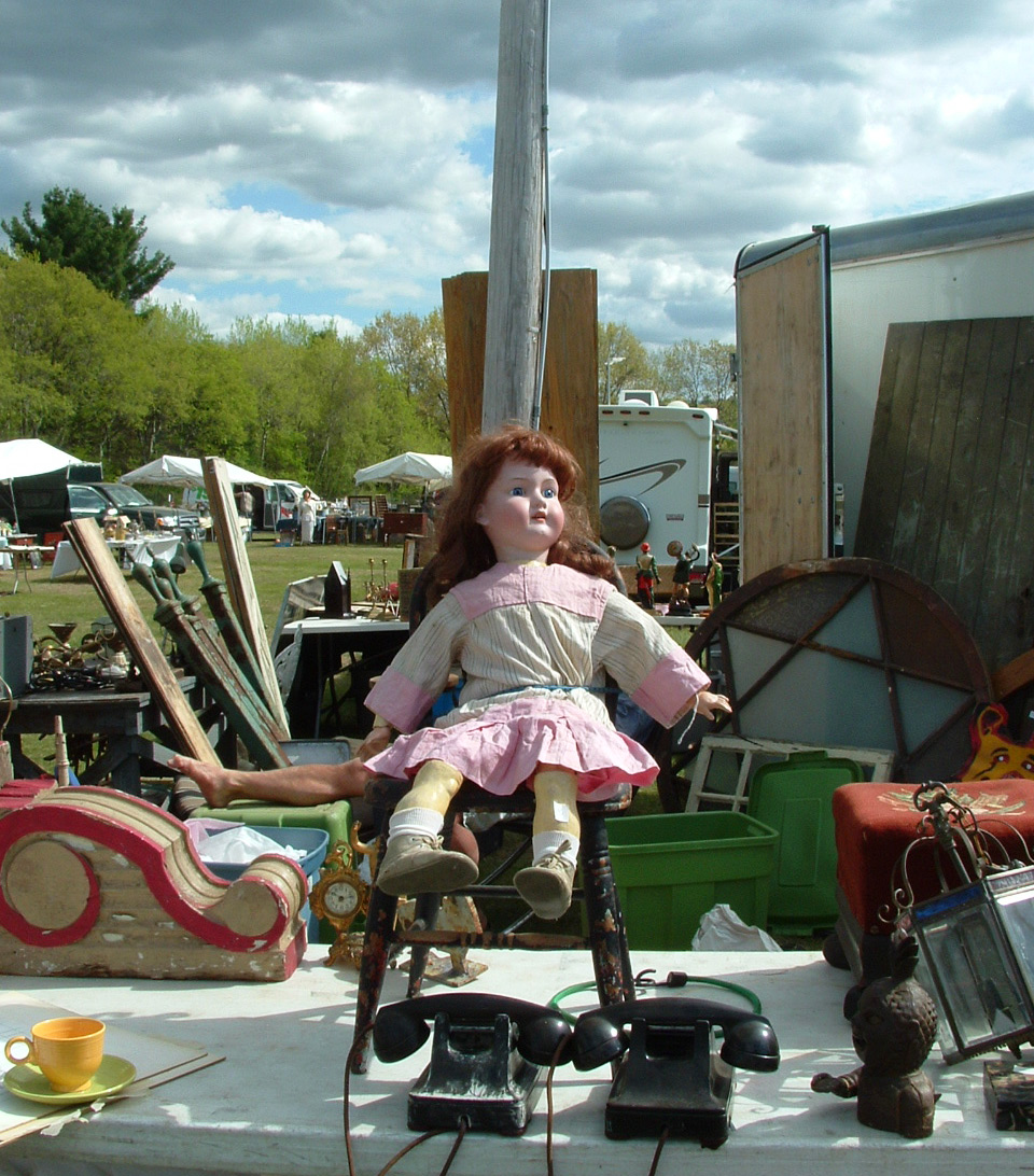 A storm brews in the background behind an antique doll at Brimfield Antique Show. Photo by Maureen Stanton.