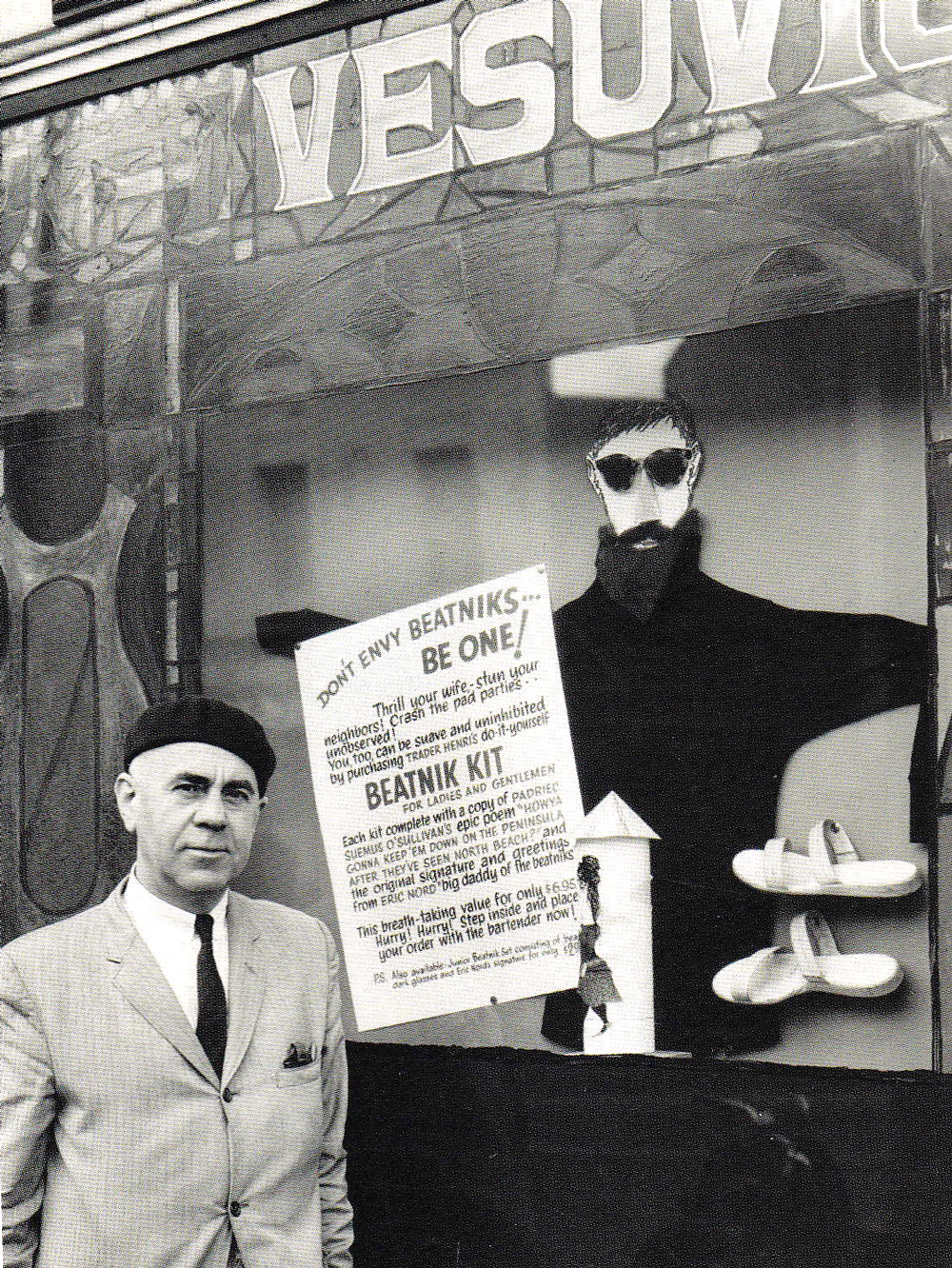 "Henri Lenoir, Cafe Vesuvio's owner, stands in front of their window with a tongue-in-cheek ad for a ""Beatnik Kit."""