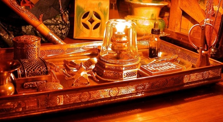 An example of an opium tray and accoutrements. The metalwork is designed to reflect the lamp light.