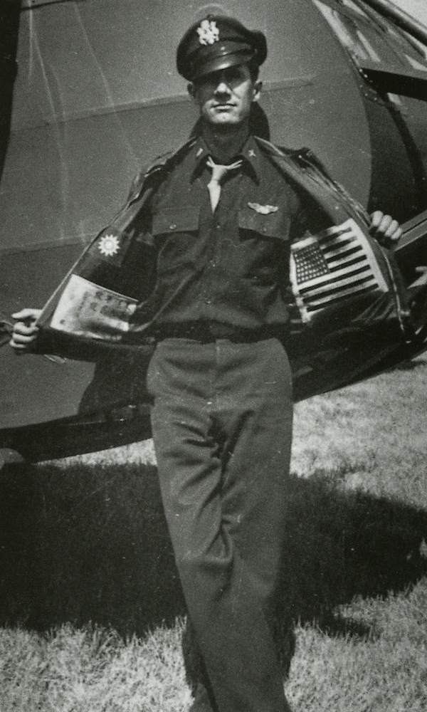 Glider pilot Nesbit L. Martin, from the 1st Air Commando, shows off his blood chits sewn inside his A-2.