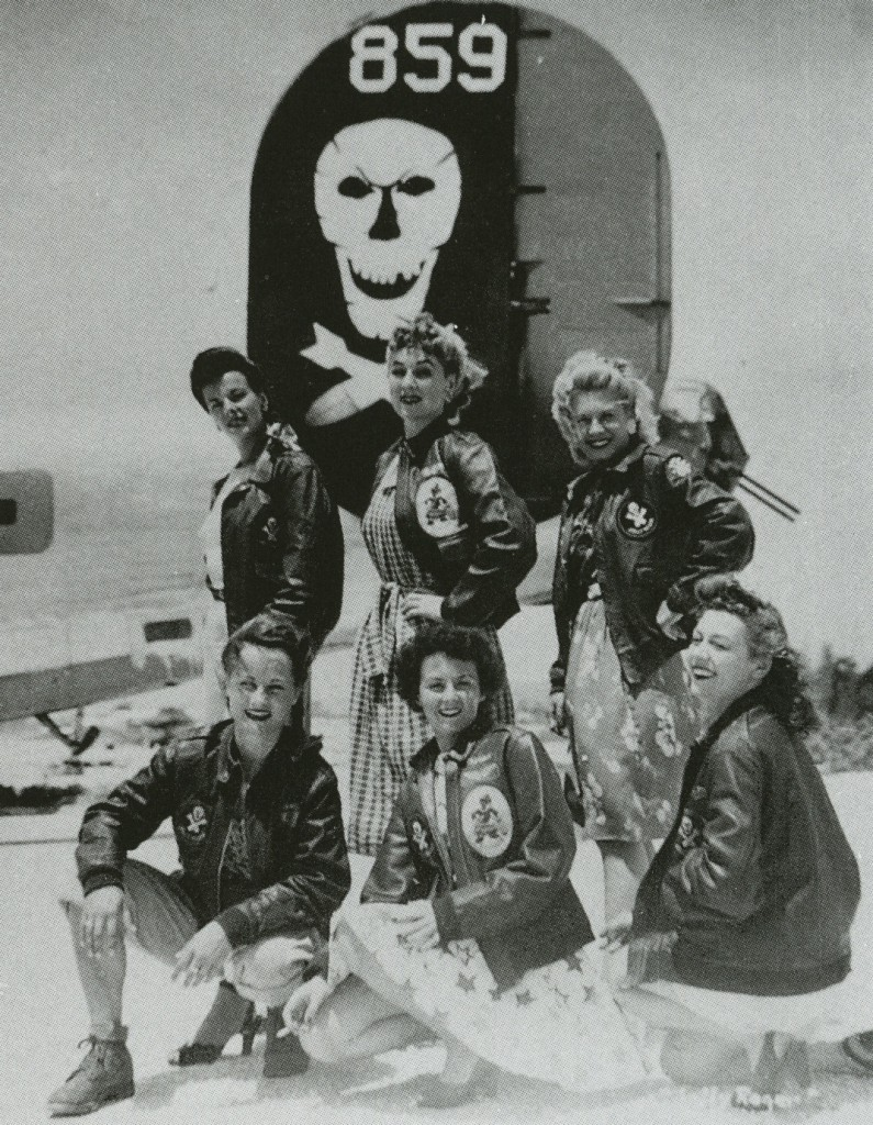 "Six U.S.O. Girls wear A-2 jackets belonging to the 90th Bomb Group, a.k.a. ""Jolly Rogers,"" under a B-24 bomber. From the collection of John Campbell."