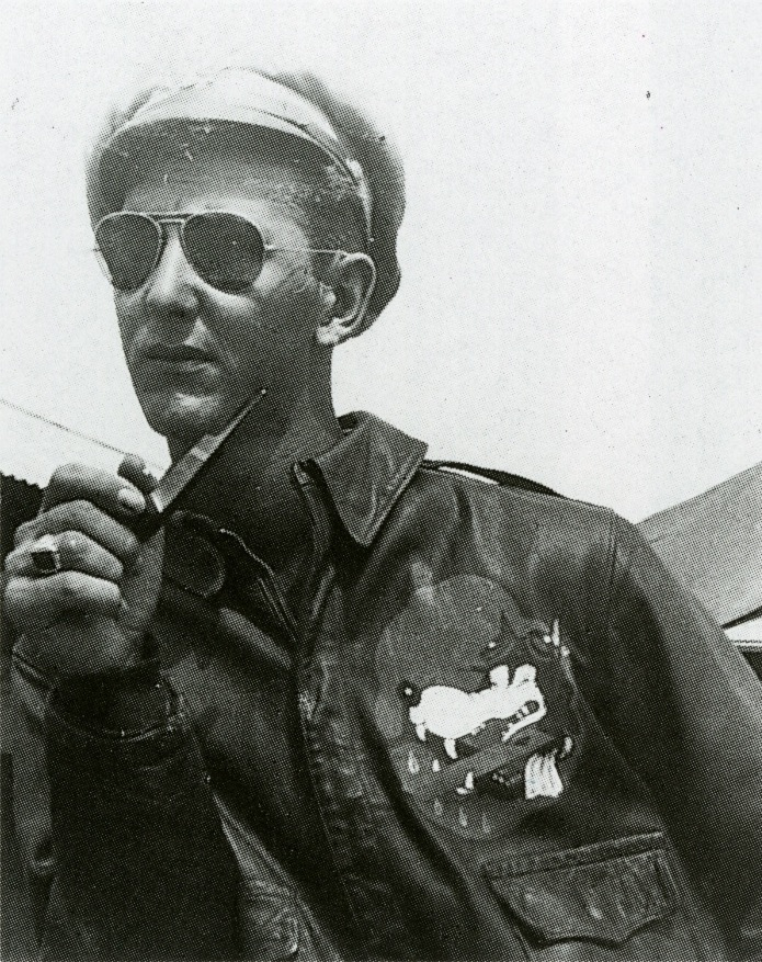 "Flight officer Robert J. Meer in Lipa, Philippines, with the ""Glider Wolf"" insignia of the 1st Glider Provisional Group painted on the front of his A-2."