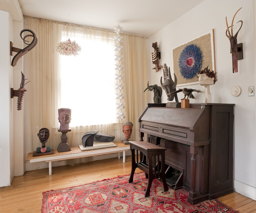 "Harper's piano room is decked with trophies, busts, and other artworks he created. Photo by Leslie Williamson, from ""Irving Harper Works in Paper."""