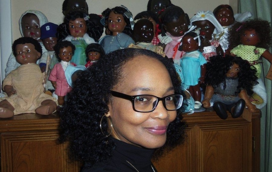 Debbie Behan Garrett poses with a group of vintage to modern dolls.