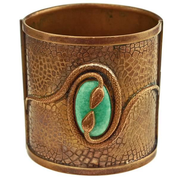"The discovery of King Tut's tomb inspired the Egyptian Revival style, which Napier adapted with this rare 1920s brass hinged cuff bracelet with a green glass cabochon and double snake motif. (From ""The Napier Co.,"" courtesy of Leslie Burke)"