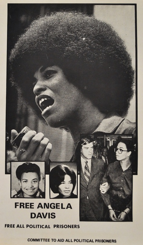Angela Davis, with a large afro, holding a mic on a poster