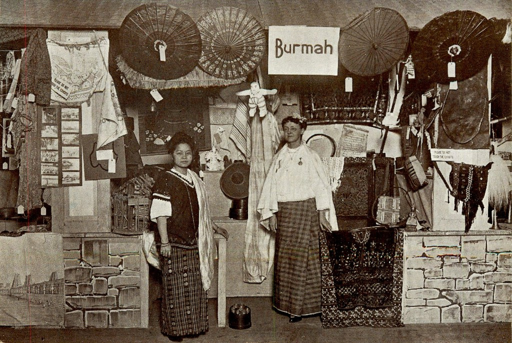 "A souvenir postcard show two women wearing native dress in the Burma Court section of 1911's missionary exposition ""The World in Boston."""