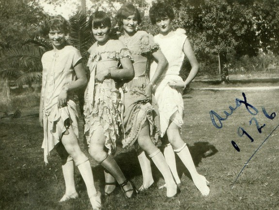 Four teenagers show off their flapper dresses and rolled-down stocking in an August 1926 snapshot.