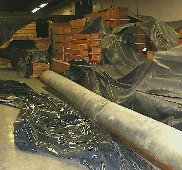 The organ's largest façade pipe is 32 feet long. Its storage on the floor of Brooks Hall has done more damage to it than the earthquake. In the background are many of the organ's wooden pipes.