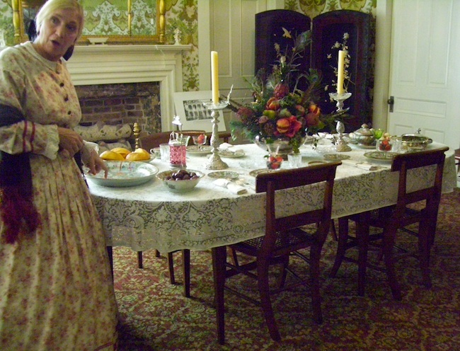 A tour guide in period garb shows the table at Hall House in Salisbury, North Carolina, built in 1820. The family of Dr. Josephus Hall, chief surgeon at the Salisbury Confederate Prison during the Civil War, owned two slave couples and their children. (Photo by Arnold Modlin)