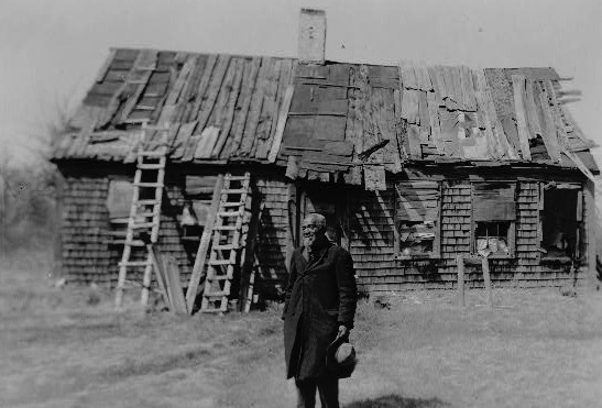 Henry Robinson, who was  interviewed for the Works Progress Administration's slave narrative project, stands in front of a dilapidated cabin in the 1930s. (Via Library of Congress)