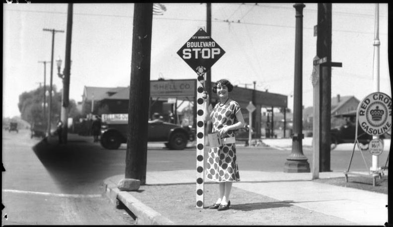 A woman poses with a newly installed stop sign in Los Angeles in 1925, built to the specifications recommended at the first National Conference on Street Safety. Via USC Libraries.