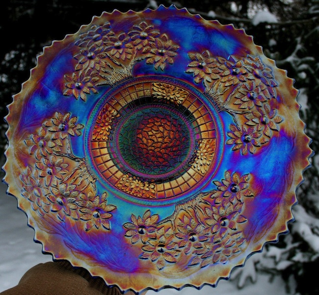 Carnival glass pieces, like this Fenton Orange Tree plate, were given away as prizes at carnivals and movie theaters in the 1910s and '20s. With orange iridescence on a base of electric blue, this plate qualifies as kitsch.