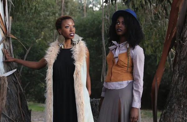 "Above: Dominique (left) and Jazmyne Drakeford model all-thrift-store looks in a redwood forest. (Photo by Pendarvis Harshaw)  Top: A woman in a Goodwill dress sits on bales of unsold clothes from the thrift store. (Photo by Shidume Lozada Photography, from ""Fashion & Sustainability"")"