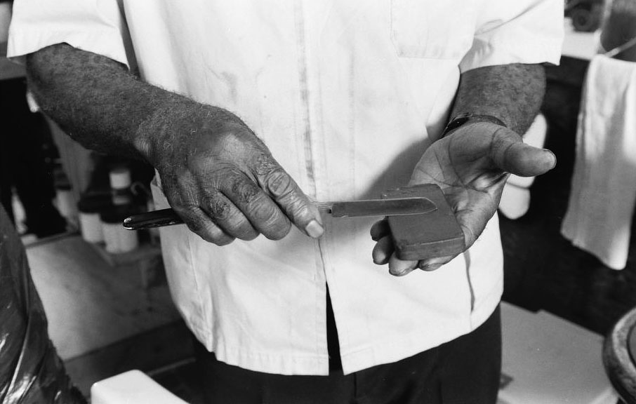 Louis McDowell demonstrates how to sharpen a straight razor at his shop in Paterson, New Jersey, in 1994. Via the Library of Congress.