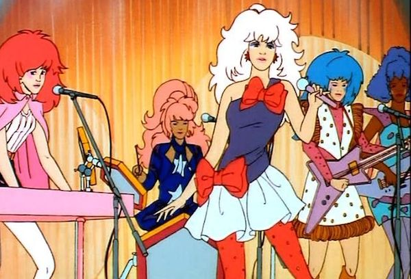 Jem and Holograms play a song in their namesake animated series. From left, Kimber on keyboards, Raya on drums, Jem on vocals, Aja on guitar, and Shana on bass. (Via Jem.wikia.com)