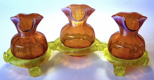 "Above: Flower vases made at the Thomas Webb & Sons factory in England. The vases rest on a Vaseline glass base. Photo via Dave Peterson at <a href=""http://www.vaselineglass.org/"">VaselineGlass.org</a> Top: The relationship between a piece of glass's propensity to glow and its uranium content is often not predictable. The piece at left contains no uranium at all, while the dark piece at bottom-center contains the most of the group. Photo via <em><a href=""http://www.schifferbooks.com/vaseline-glassware-fascinating-fluorescent-beauty-3468.html"">Vaseline Glassware</a></em> by Barrie Skelcher."