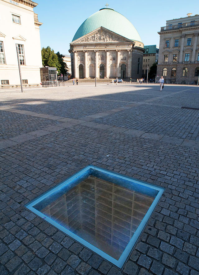 In Berlin's Bebelplatz, this memorial by Micha Ullman recalls the Nazi book-burning of 1933 with its rows of empty, white shelves permanently embedded into an underground room. (via Wiki Commons)