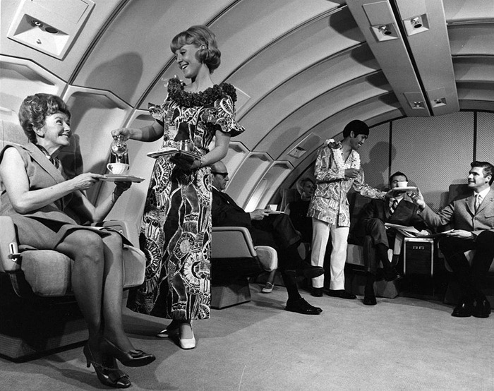 In a 1970s promotional photo for United, flight attendants wear muumuus, aloha shirts, and leis onboard a flight to Hawaii. (Via Museum of Flight)